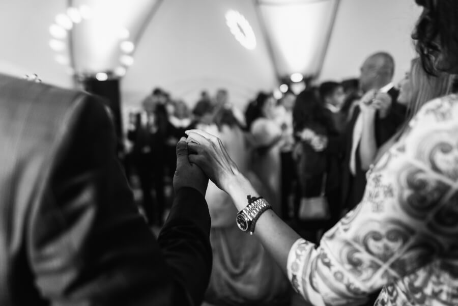 Man and woman hold their hands up while dancing